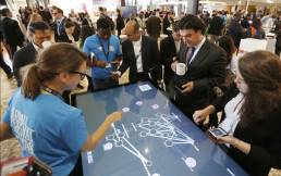 A group of people around a touch screen showing an interactive network of policies and goals at the Global Festival of Ideas.