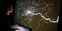 A visitor interacts with London Data Streams installation by Tekja at Big Bang data exhibition at Somerset House
