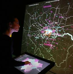 Visitor interacting with a map touch screen in the London Data Streams exhibition by Tekja at Somerset House