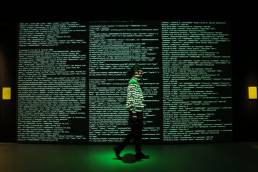 A woman walks through the installation awash with real-time data